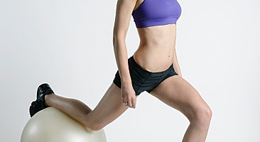 Woman exercising legs with fitness ball lunges